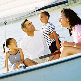 family sitting in boat on lake