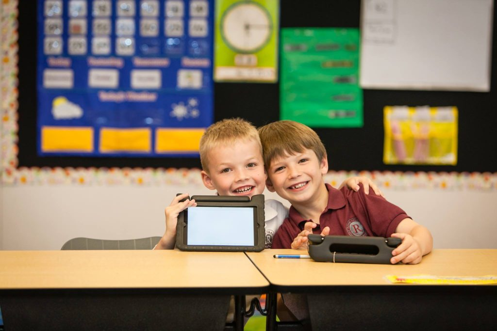 two kids with tablets in classroom at River Islands